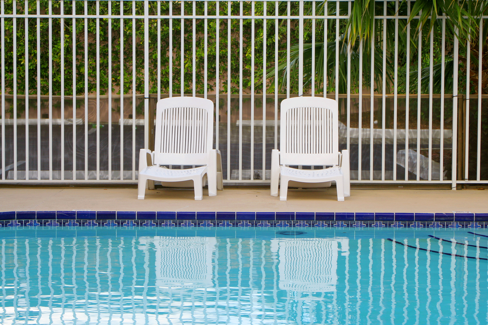 Plastic chairs sitting in front of a swimming pool fence
