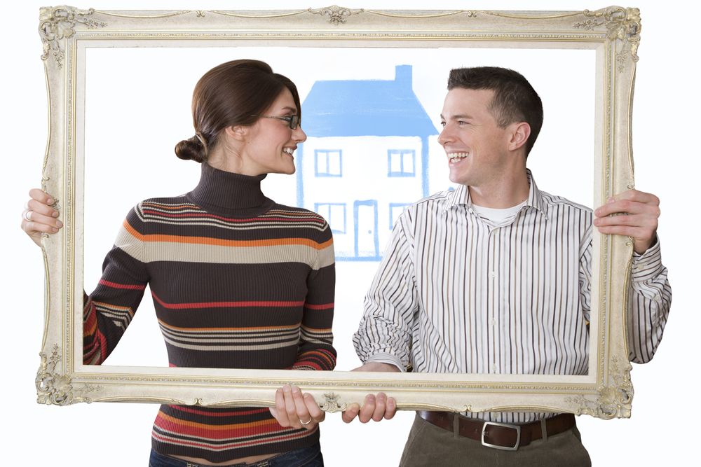 Smiling couple hold an empty frame with a house in background