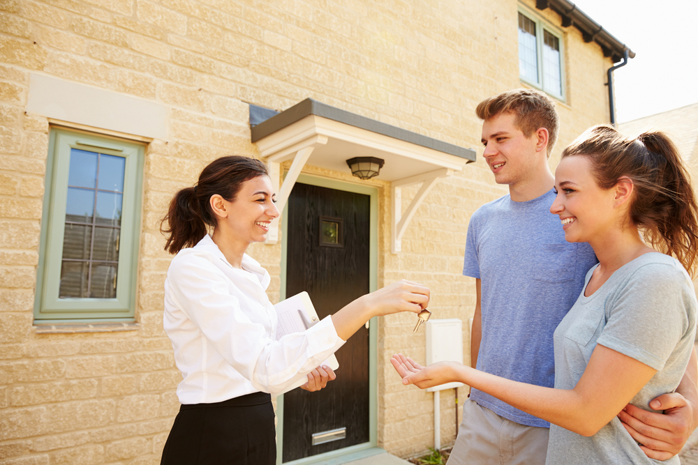 A property manager hands over the keys to tenants