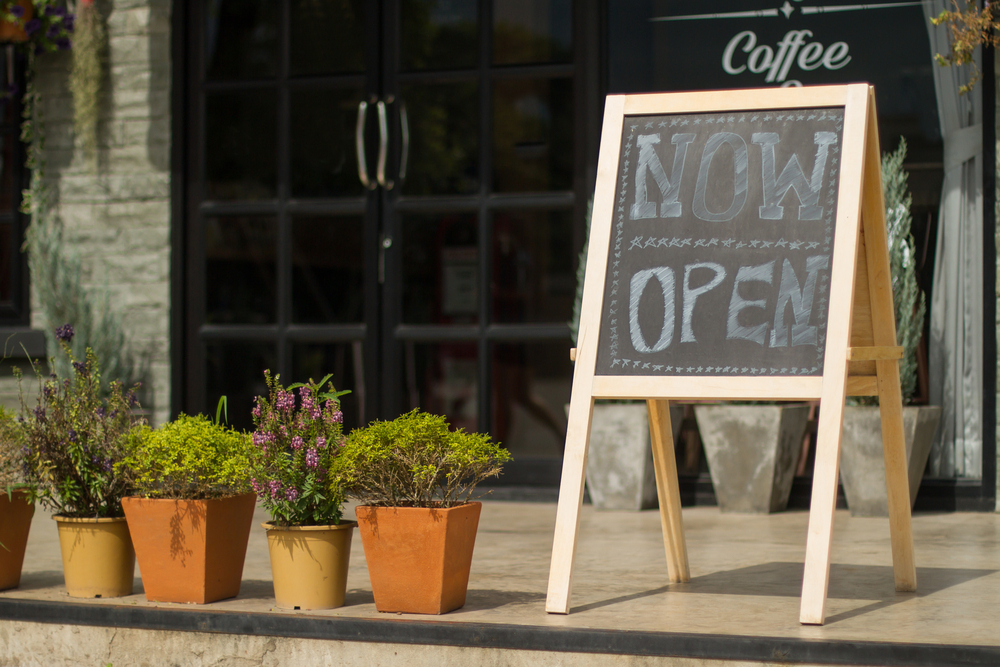 "A shopfront with a ""now open"" blackboard sign"